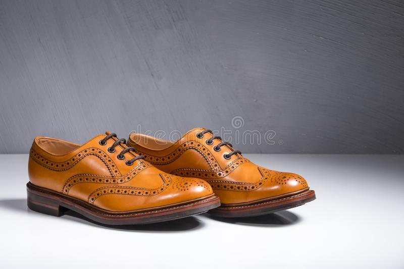 Closeup of Pair of Luxury Male Full Broggued Tan Leather Oxfords. Shoes On White Surface. Against Gray Wall. Horizontal Image royalty free stock photography