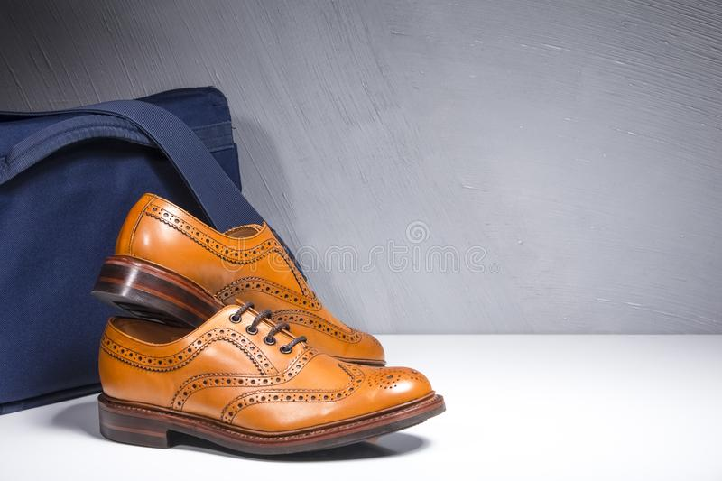 Closeup of Pair of Luxury Male Tanned Full Broggued Oxford Calf. Leather Shoes Along Messenger Blue Bag on White Surface. Horizontal Image stock image