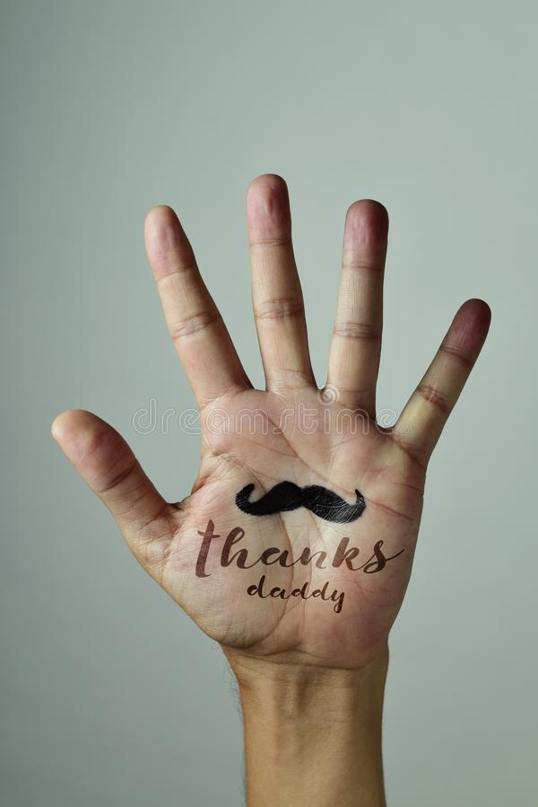Text thanks daddy and mustache on a mens hand. Closeup of the palm of the hand of a young caucasian man with a mustache and the text thanks daddy written in it royalty free stock photo
