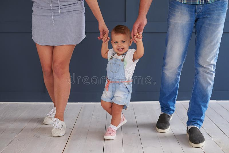 Parents teaching cute little daughter to walk in room stock image