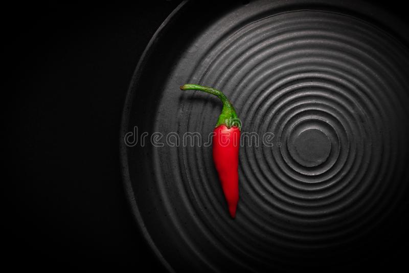 Closeup part of round black ceramic plate with pattern of circles, red fresh chili peppers. Concept stylish modern stock images