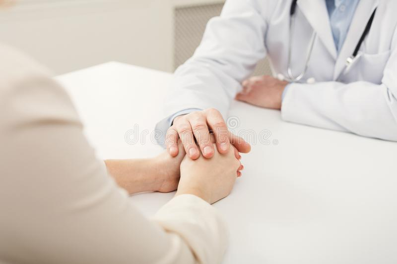 Closeup of patient and doctor hands. In hospital. Doctor consulting and supporting female patient, healthcare and medical concept, copy space stock image