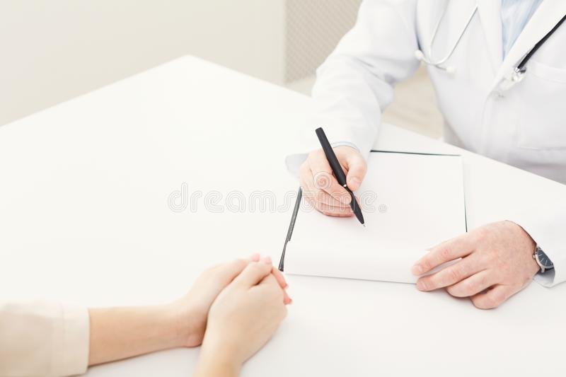 Closeup of patient and doctor taking notes stock photos