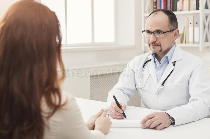 Closeup of patient and doctor taking notes royalty free stock photo