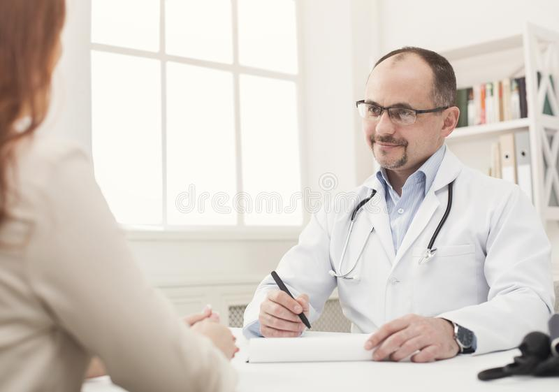 Closeup of patient and doctor taking notes royalty free stock images