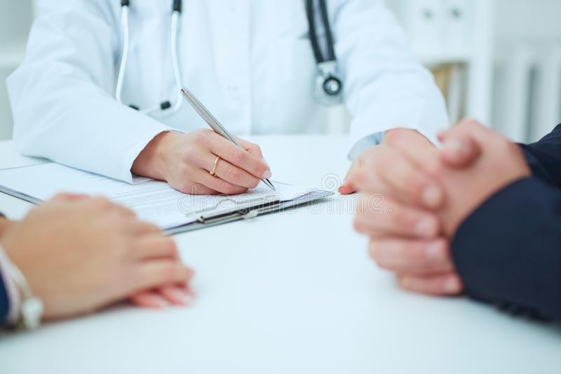 Closeup of couple patients hands and doctor taking notes. Medical family counseling concept. stock image