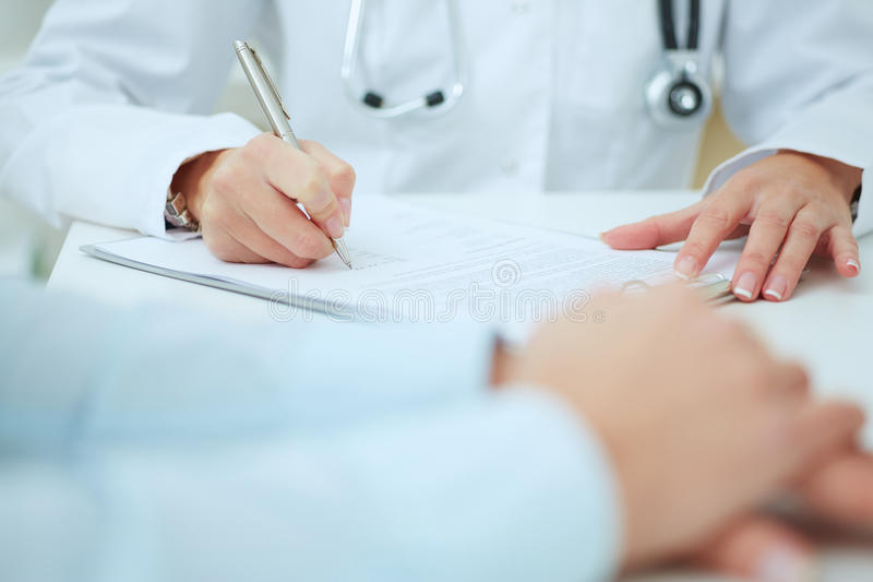 Closeup of patients hands and doctor taking notes. stock photo