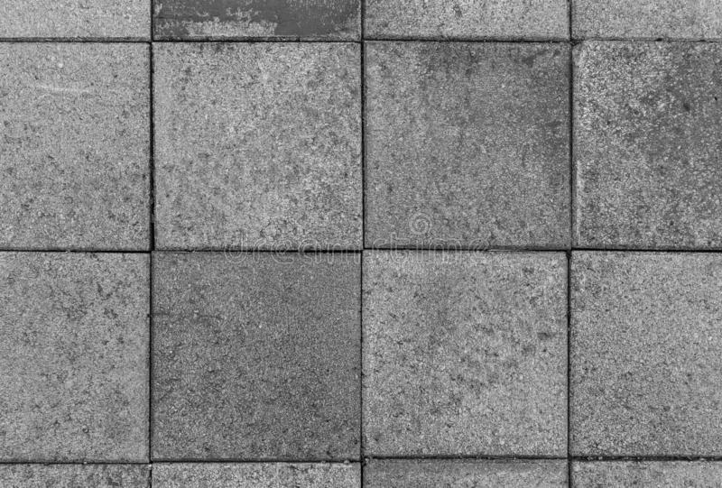 Closeup of paving stones from above in black and white. Close-up of a bit dirty and weathered square paving stones or blocks outdoors viewed from above in black royalty free stock image