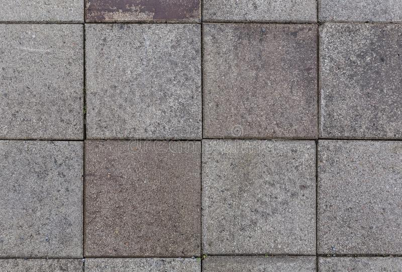 Closeup of paving stones from above. Close-up of a bit dirty and weathered square paving stones or blocks outdoors viewed from above. High resolution full frame stock photos