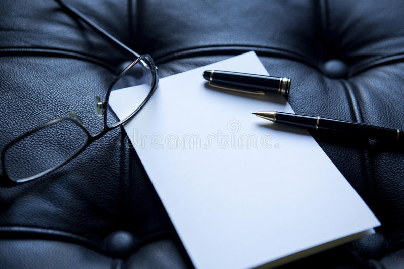 Closeup of pen and paper on black leather royalty free stock images