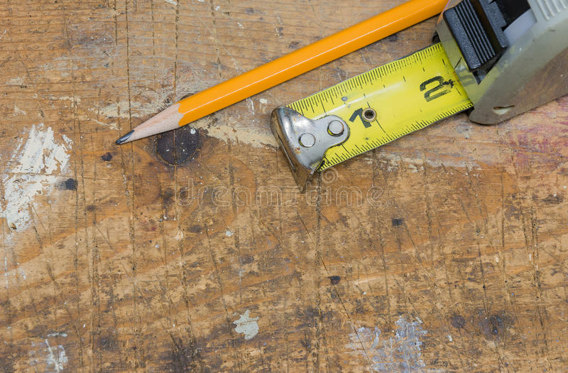 Closeup of pencil and tape measure on scratched and worn wooden. Workshop bench surface royalty free stock images