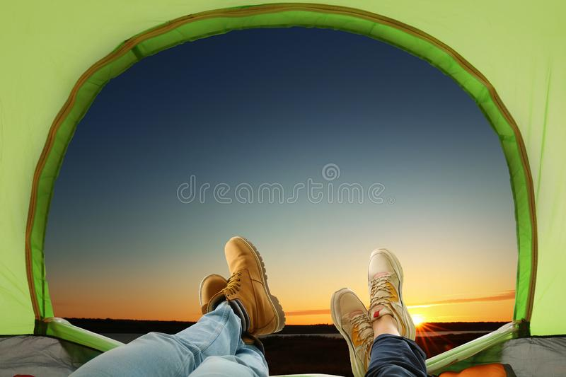 Closeup of people in camping tent near river at sunset. View from inside royalty free stock photography