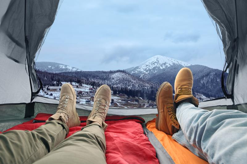 Closeup of people in camping tent on snowy mountain hill. View from inside royalty free stock image