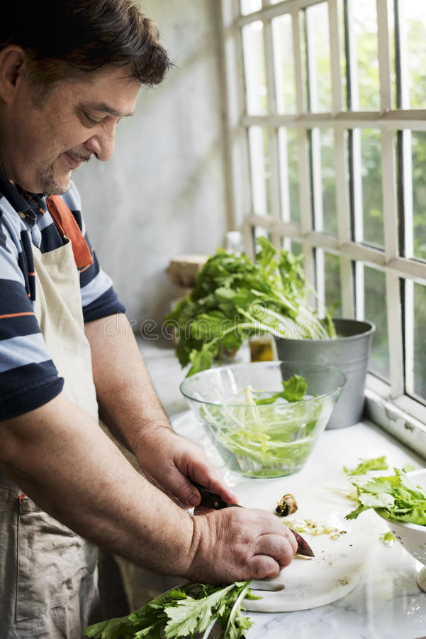 Closeup of people preparing vegetable to be cooked in the kitchen stock image