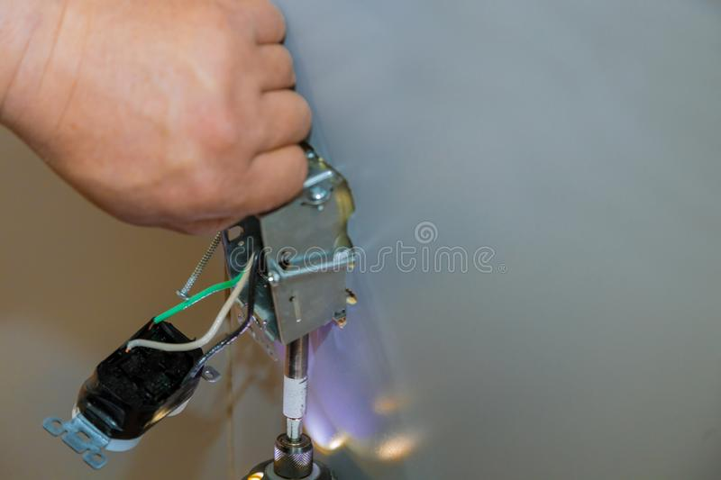 Closeup of a person`s hand fixing an electronic device on a gray wall. A closeup of a person`s hand fixing an electronic device on a gray wall stock photography