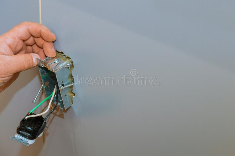 Closeup of a person`s hand fixing an electronic device on a gray wall. A closeup of a person`s hand fixing an electronic device on a gray wall royalty free stock photos
