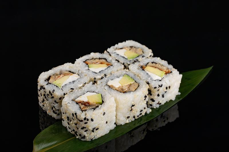Closeup philadelphia roll sushi with eel cucumber, cream cheese and sesame seeds served on black background stock image