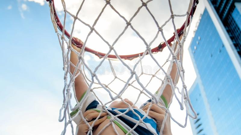 Closeup photo of active 3 years old toddler boy holding on basketball net ring. Concept of active and sporty children stock photos