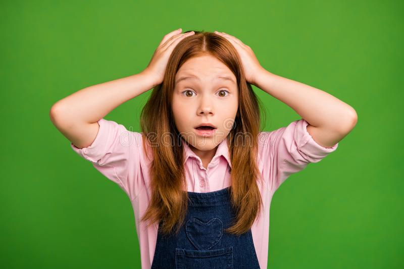 Closeup photo of adorable little ginger schoolchild in front of blackboard don`t know forgot answer on teacher question. Wear denim, overall pink shirt isolated royalty free stock photography