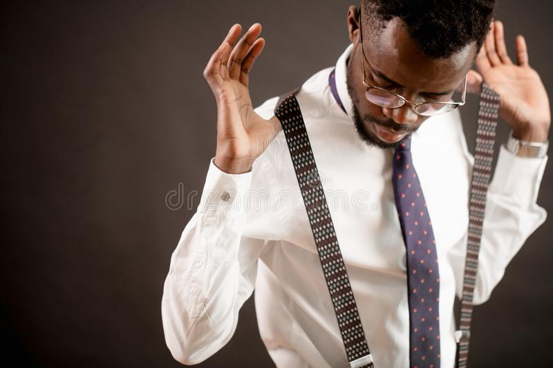 Closeup photo of african groom putting on slenders before wedding stock images