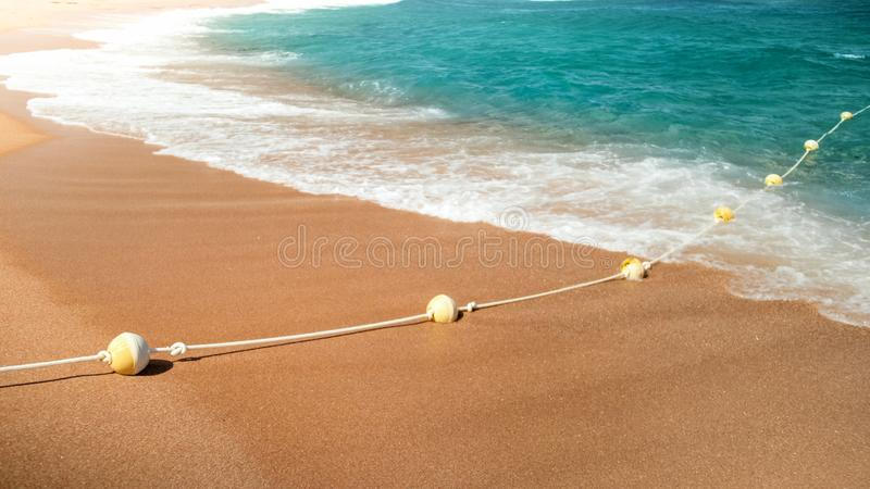 Closeup photo of beatiful sandy sea beach and waves rolling over life buoys line on the rope stock photos