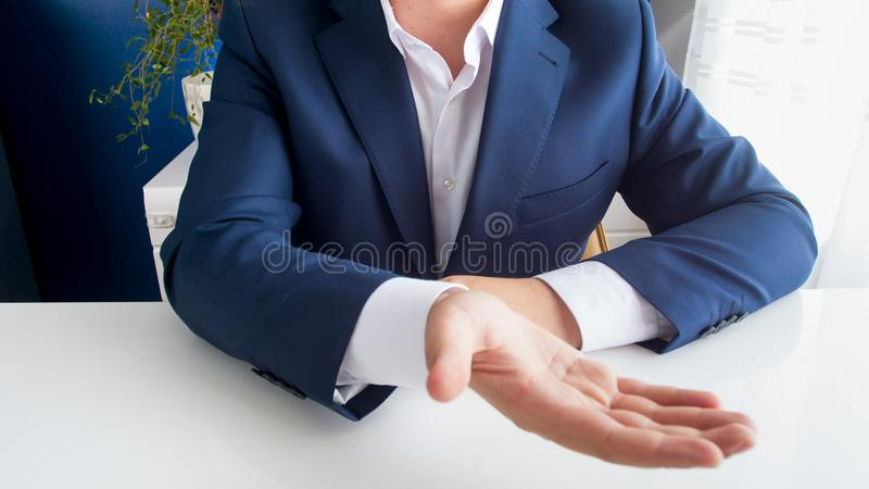 Closeup image of businessman sitting behind office desk stretching hand and asking for money stock images