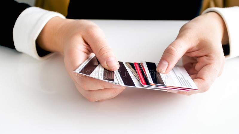 Closeup image of busineswoman sitting behind desk and holding big stack of credit cards. Closeup photo of busineswoman sitting behind desk and holding big stack royalty free stock photography