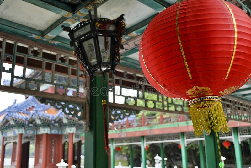 Chinese Hanging Red Lantern Closeup. A closeup photo of a Chinese hanging red lantern under a pagoda with carvings, art, and architecture in the background stock image