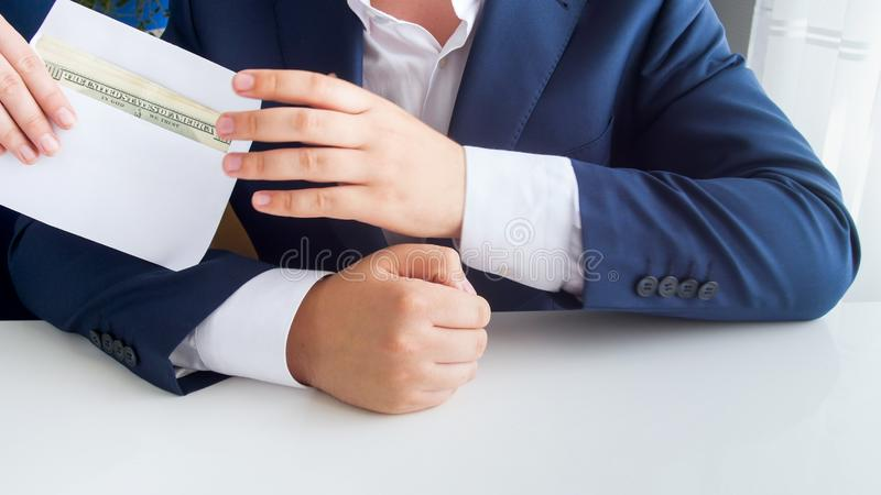 Closeup image of corrupted official receiving bribe in envelope at office. Closeup photo of corrupted official receiving bribe in envelope at office stock images
