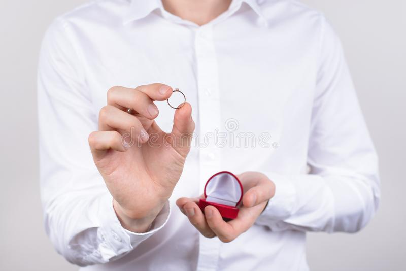 Closeup photo cropped picture of happy cheerful excited glad positive optimistic guy holding small little ring in hand with royalty free stock images