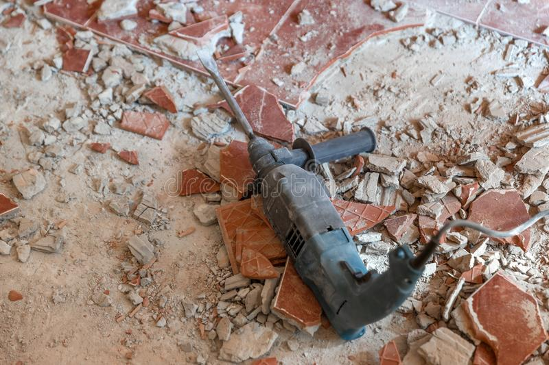 Closeup photo of an electric industrial drilling equipment. On demolished floor stock photo