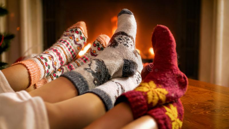 Closeup image of family in knitted woolen socks lying on sofa at living room with fireplace. Closeup photo of family in knitted woolen socks lying on sofa at royalty free stock photo