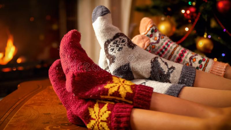 Closeup image of family in warm knitted socks lying next to fireplace and Christmas tree stock images