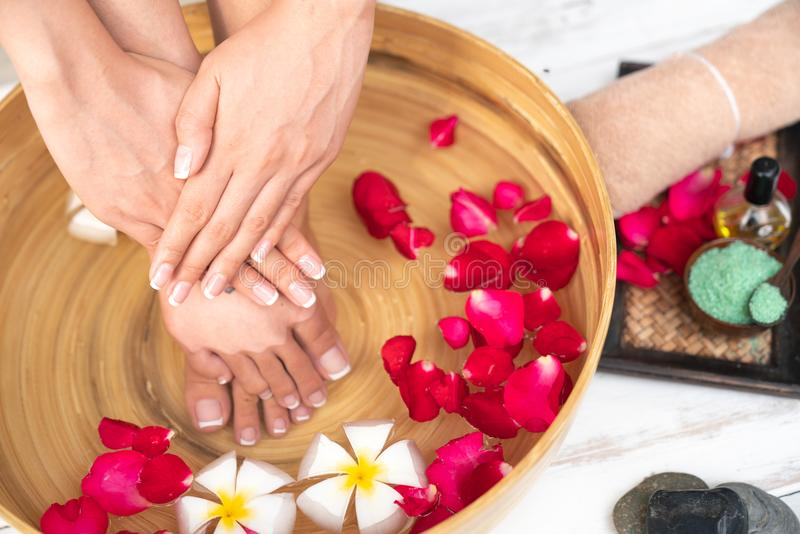 Closeup photo of a female feet at spa salon on pedicure procedure. Female legs in water decoration the flowers. royalty free stock photography