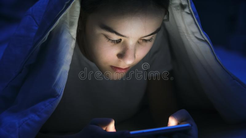 Closeup photo of girl in pajamas browsing internet on smartphone under blanket at night royalty free stock photo
