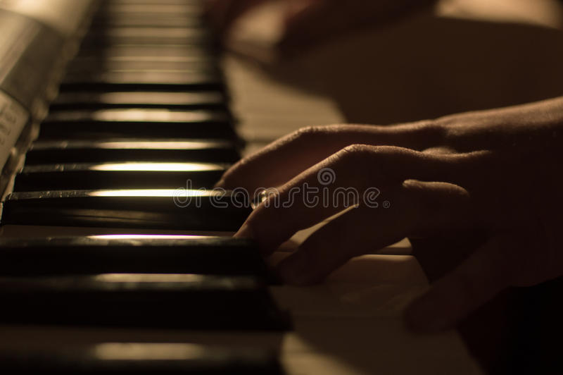 Closeup photo of a hand playing the piano keys. Concept: Music creating, composing, lyrics, performance. Closeup soft focused atmospheric photography of a hand royalty free stock photo