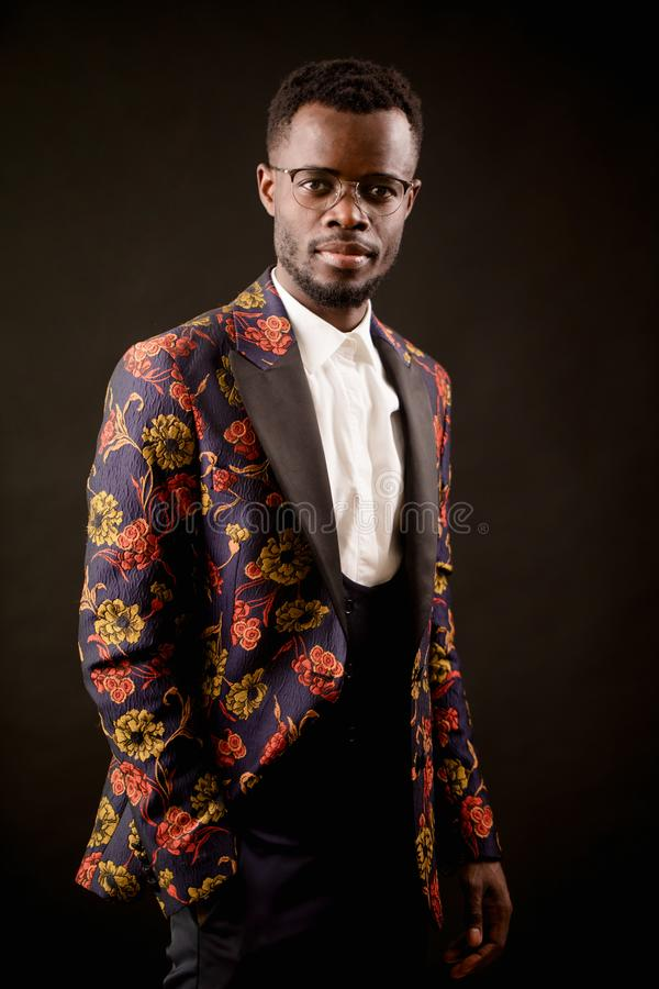 Closeup photo of handsome African fashion model in a unusual suit. stock photo