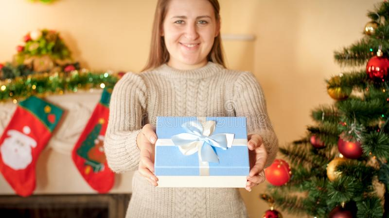 Closeup photo of happy smiling young woman giving Christmas present in beautiful box with silk ribbon bow royalty free stock photo