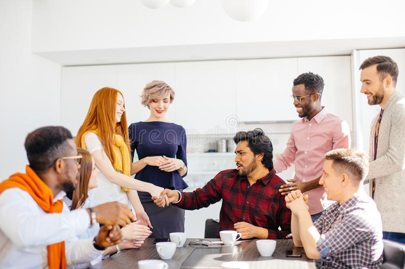 Hindoo employee giving a warm handshake to smiling red-haired woman. Closeup photo of Hindoo employee giving a warm handshake to smiling red-haired women in royalty free stock photography