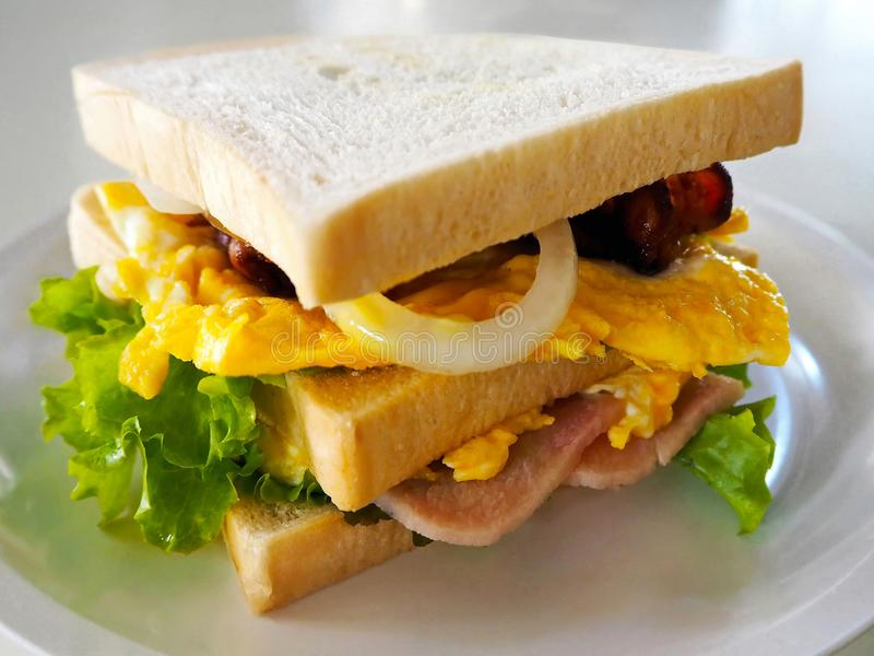 Homemade Club Sandwich on the White Plate. Closeup photo of homemade club sandwich with ham, bacon, egg and vegetables royalty free stock images