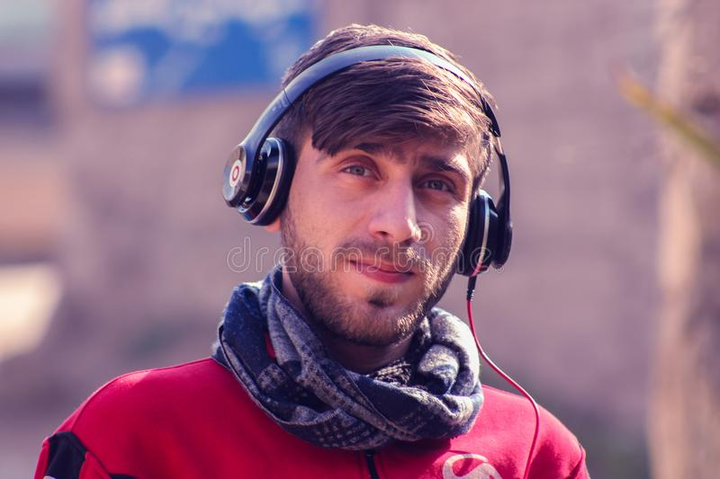 Closeup Photo of a Man Wearing Red Top, Gray Scarf, and Black Beats by Dr. Dre Headphones royalty free stock images