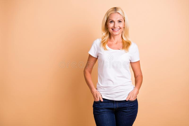 Closeup photo of middle age lady smiling neat appearance wear white casual t-shirt jeans denim isolated pastel beige royalty free stock photography