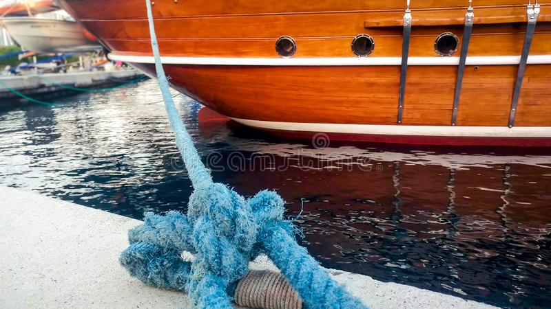 Closeup photo of old big rope mooring historic wooden ship at port stock photography