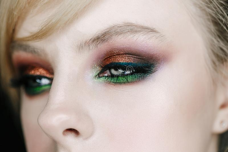 Closeup photo of opened woman eye with beautiful bright makeup, brown and green smoky eyes looking right side stock photography