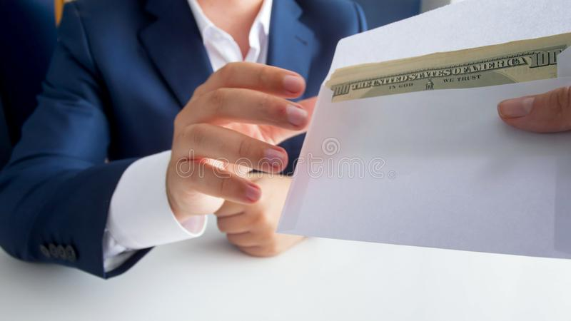 Closeup image of person giving envelope with money to bribed politician royalty free stock image