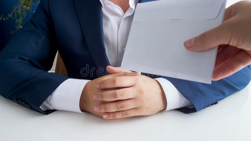 Closeup photo of person giving envelope to corrupted politician in office. Closeup image of person giving envelope to corrupted politician in office stock photo