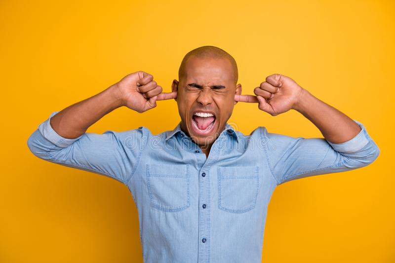 Closeup photo portrait of angry irritated with open mouth bald guy closing ears with forefingers isolated vivid royalty free stock image