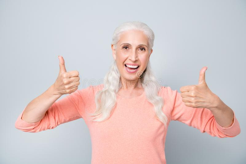 Closeup photo of positive optimistic having good mood granny giving double fingers up wearing peach color pullover royalty free stock photo