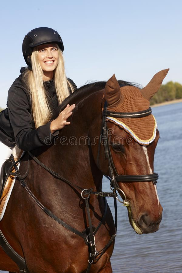 Closeup photo of rider and horse. Closeup photo of young female rider leaning over horse at riverside royalty free stock photo