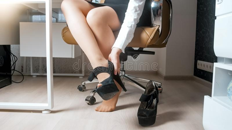 532378aabfa Young Businesswoman In Pantyhose Taking Off Uncomfortable High Heels ...